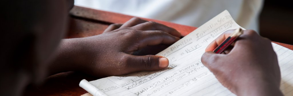 Photo of a school kid in Tanzania writing at his desk