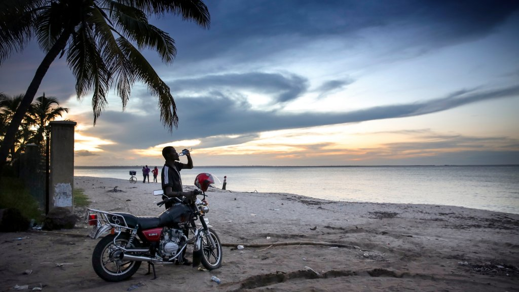 A man on a motorbike at a beach looking at the sunset
